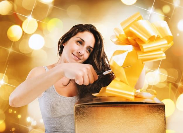 Het meisje bereidt de boog van een grote giftdoos op gouden muur voor