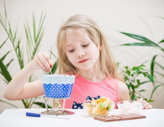 Het meisje bereidt een smakelijke traktatie bij de kaarsvlam.