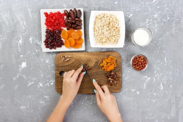 Het meisje bereidt haar ontbijt voor. het meisje snijdt haar dadelfruit in havermoutpap op een snijplank. handig en gezond ontbijt op een grijze, bovenaanzicht