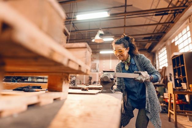 Het meisje bereidt houten plank voor verwerking op houtbij voor, dragend beschermend materiaal.