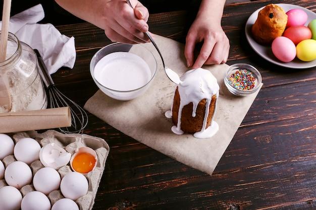 Het meisje bereidt pasen bakken, smeert de cake met ijsvorming en bestrooit met gekleurd poeder. voorbereiding op de vakantie op de keukentafel op donker.