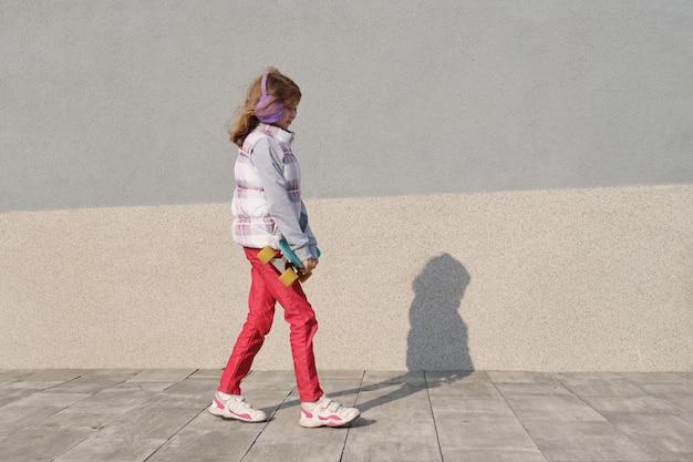 Het meisje berijdt een skateboard, op gebied dichtbij het huis, lentetijd