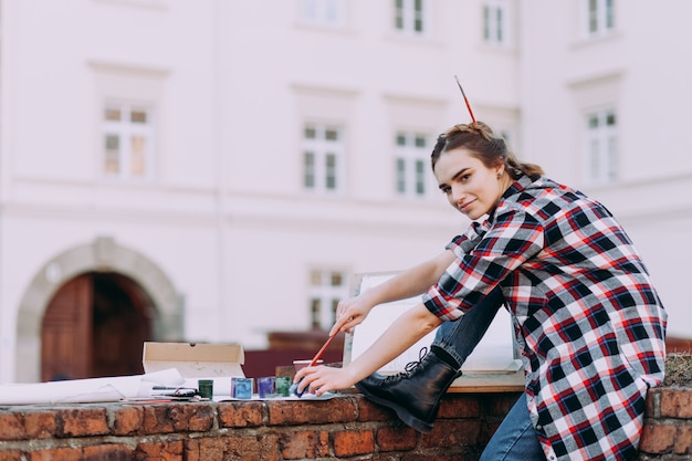 Het meisje besteedt vrije tijd aan het tekenen van foto's op een stadsstraat.