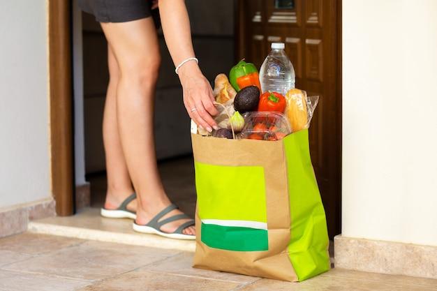 Het meisje bestelde boodschappen aan huisbezorging van boodschappen aan de handenbezorging van producten in ambacht
