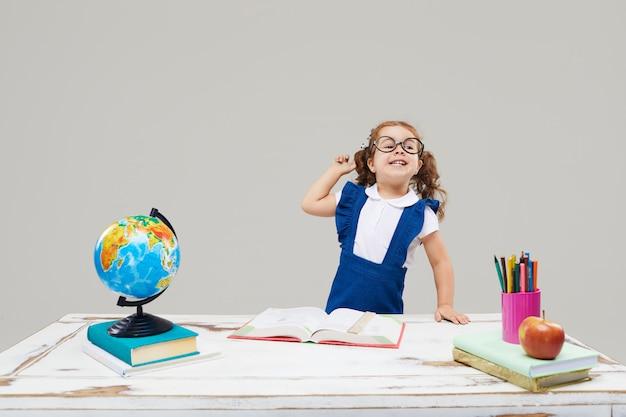 Het meisje bestudeert terwijl het dragen van een afstuderen cap op een grijze geïsoleerde muur