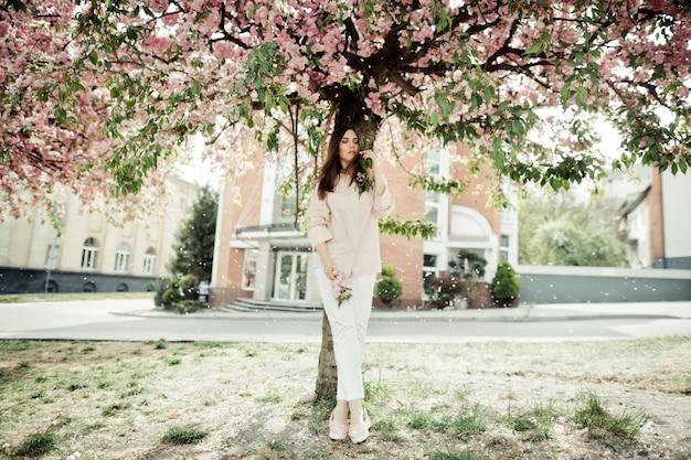 Het meisje bevindt zich dichtbij een sakuraboom bij de bouw
