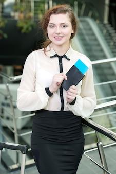 Het meisje bevindt zich op de luchthaven met kaartjes en het glimlachen.