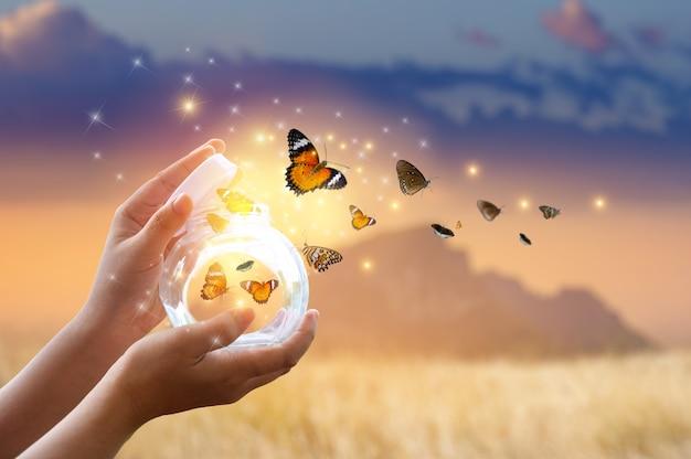 Het meisje bevrijdt de vlinder uit de pot, goudblauw moment concept van vrijheid