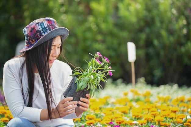 Het meisje bewondert de bloemen in de tuin.