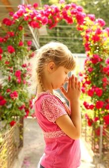 Het meisje bidt op aard met roos