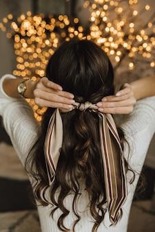 Het meisje bindt sjaal op haar haar