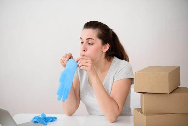 Het meisje blaast een handschoen alvorens haar hand tegen de ruimte van dozen aan te trekken