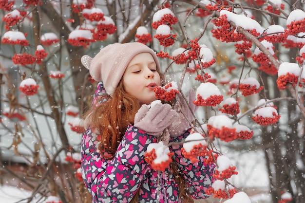 Het meisje blaast sneeuw van een lijsterbessentak weg.