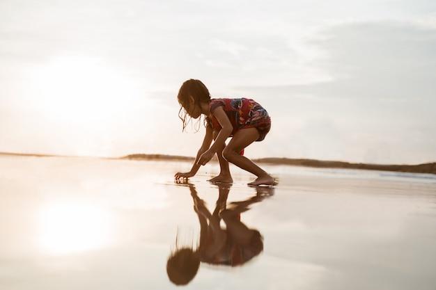 Het meisje boog zich voorover en speelde zand op het strand