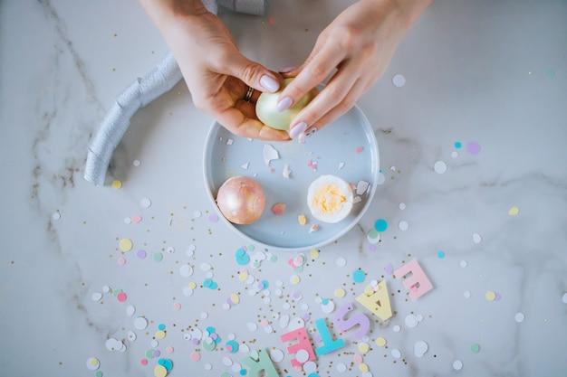 Het meisje breekt gouden paaseieren op marmeren achtergrond, confettien, fonkelingen, linten.