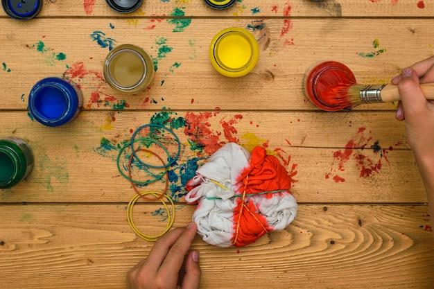 Het meisje brengt rode verf op de stof in de stijl van tie-dye