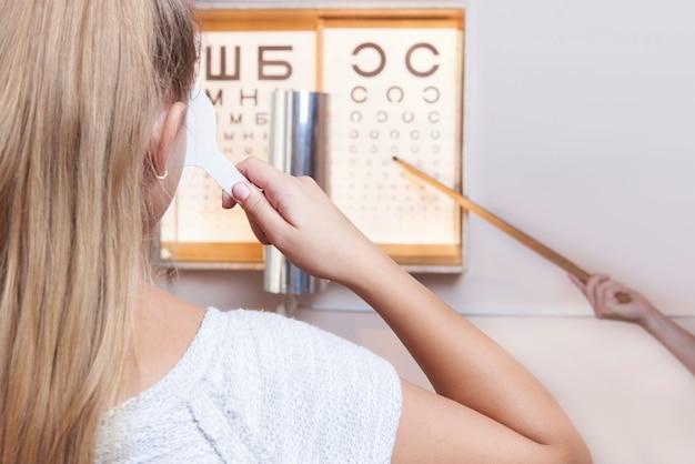Het meisje controleert het gezichtsvermogen in het ziekenhuis.