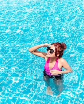 Het meisje dat bikini of swimwear draagt zonnebaadt bij de pool.