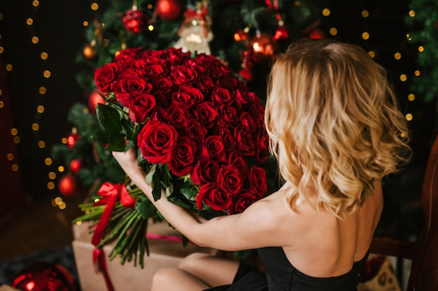 Het meisje dat de blondine in haar handen houdt, honderd en een roos
