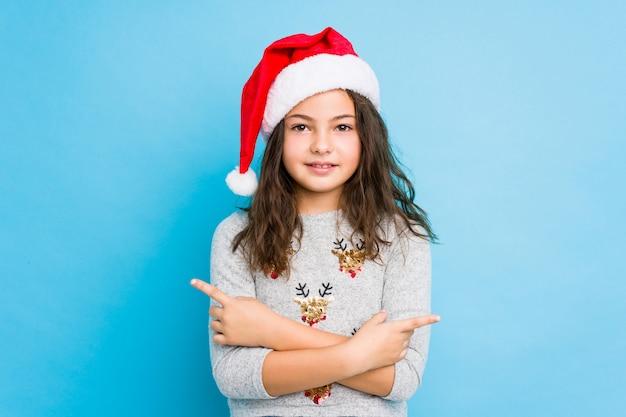 Het meisje dat de punten van de kerstmisdag zijdelings viert, probeert tussen twee opties te kiezen.