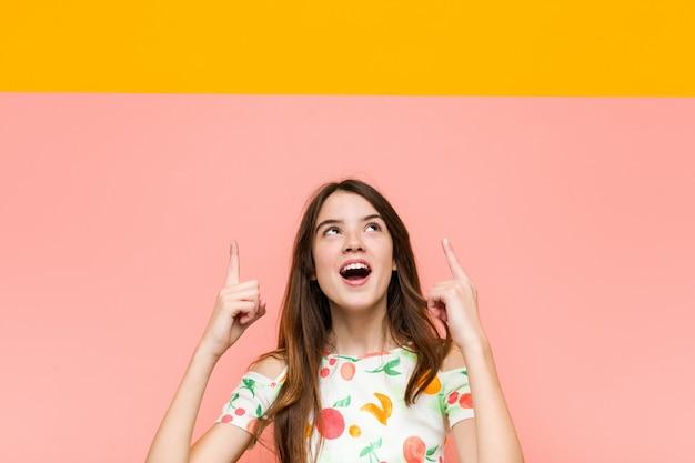 Het meisje dat de zomer draagt kleedt wijzend bovenkant met geopende mond