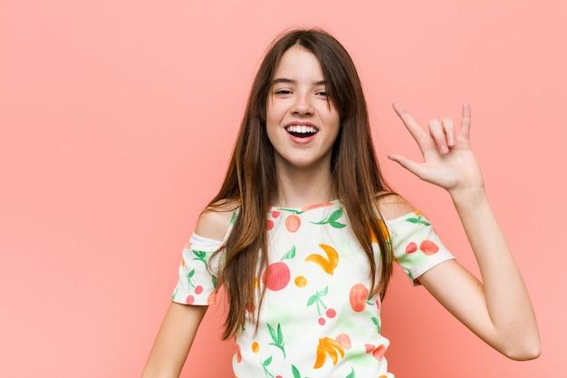 Het meisje dat de zomer draagt kleedt zich tegen een muur die een hoornengebaar toont als revolutie.