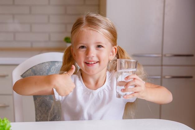 Het meisje dat duimen toont ondertekent omhoog en houdt een transparant glas. kind raadt drinkwater aan. goede gezonde gewoonte voor kinderen. gezondheidszorg concept