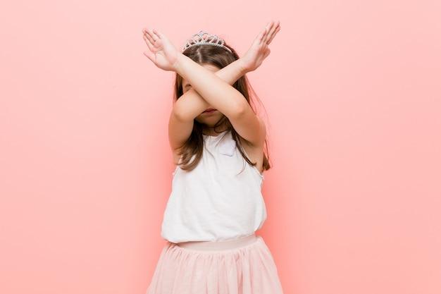 Het meisje dat een prinses draagt kijkt en houdt twee armen gekruist, ontkenning.