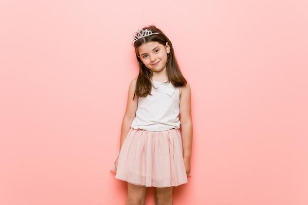 Het meisje dat een prinses draagt kijkt gelukkig, glimlachend en vrolijk
