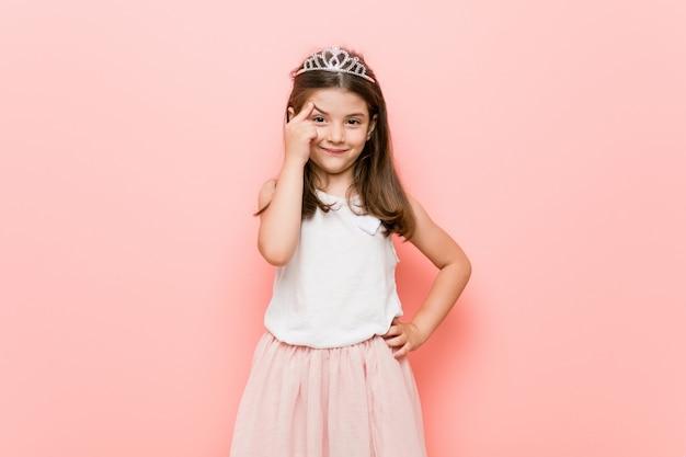 Het meisje dat een prinses draagt kijkt het denken