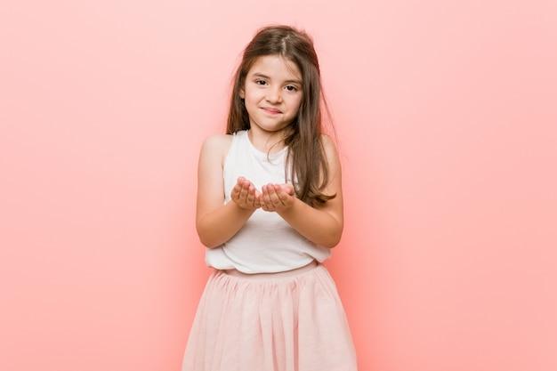 Het meisje dat een prinses draagt kijkt het houden van iets met palmen, het aanbieden.