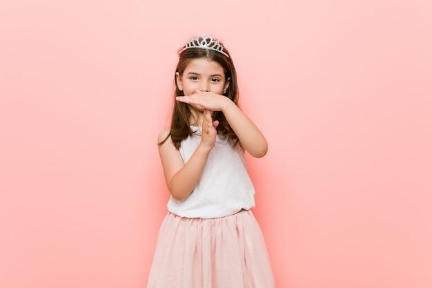 Het meisje dat een prinses draagt kijkt het tonen van een onderbrekinggebaar.