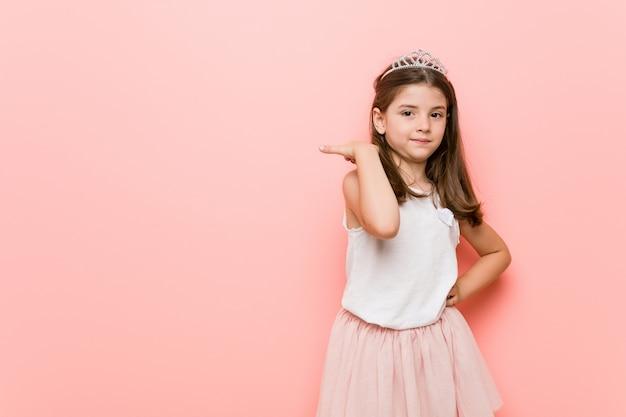 Het meisje dat een prinses draagt kijkt met duimvinger weg, lachend en onbezorgd.