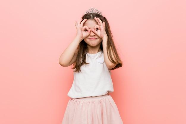 Het meisje dat een prinses draagt kijkt ok teken over ogen tonend
