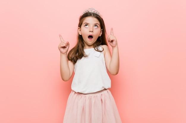 Het meisje dat een prinses draagt kijkt ondersteboven met geopende mond.