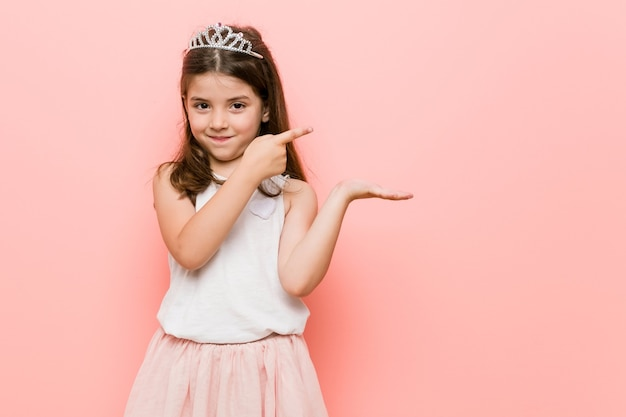 Het meisje dat een prinses draagt kijkt opgewonden met een exemplaarruimte op palm. Premium Foto