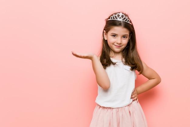 Het meisje dat een prinses draagt kijkt tonend met een hand op taille