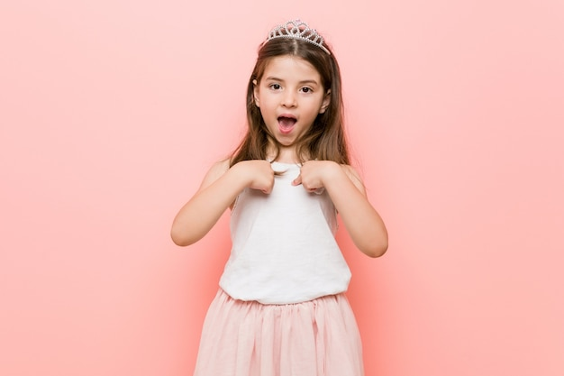 Het meisje dat een prinses draagt kijkt verbaasd wijzend met vinger, breed glimlachend