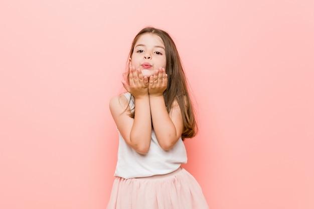 Het meisje dat een prinses draagt kijkt vouwende lippen en houdt palmen vast om luchtkus te verzenden