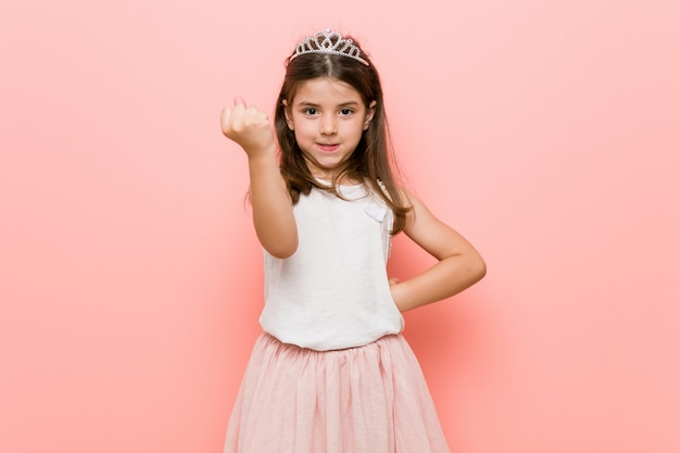Het meisje dat een prinses draagt kijkt vuist tonen aan met agressieve gelaatsuitdrukking.