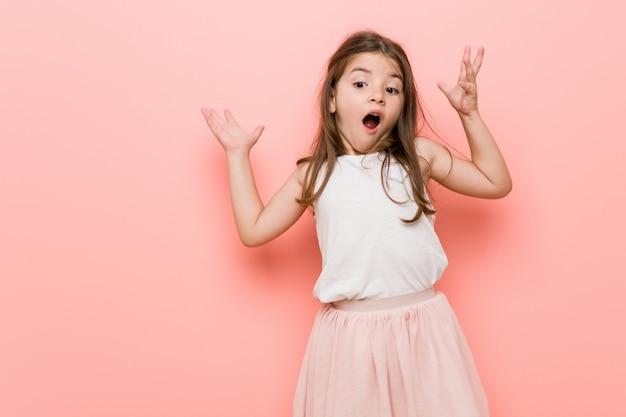 Het meisje dat een prinses draagt, ontvangt een aangename verrassing, opgewonden en opheffende handen.