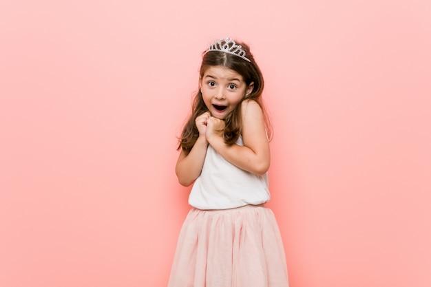 Het meisje dat een prinses draagt ziet er bang en bang uit.
