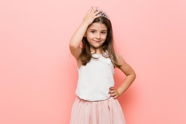 Het meisje dat een prinses draagt, ziet er moe en slaperig uit en houdt de hand op het hoofd.