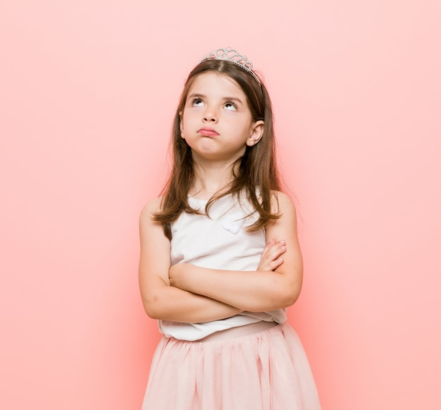 Het meisje dat een prinses draagt ziet er moe uit van een repetitieve taak.