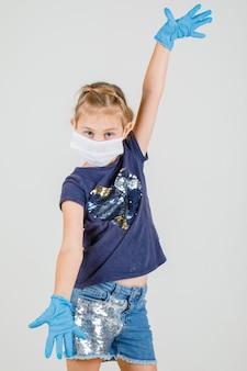 Het meisje dat groot grootteteken toont met dient t-shirt, rok en masker vooraanzicht in.