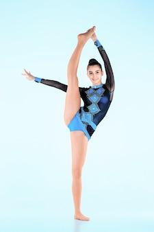 Het meisje dat gymnastiekdans doet op een blauwe muur