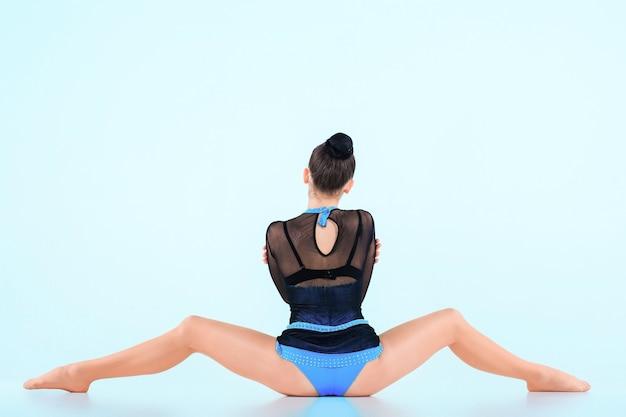 Het meisje dat gymnastiekdans doet op een blauwe ruimte