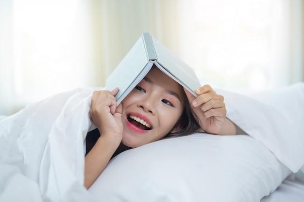 Het meisje dat in bed ligt dat aan muziek luistert en boeken leest.