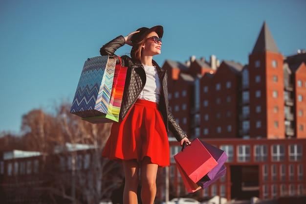 Het meisje dat met het winkelen op stadsstraten loopt
