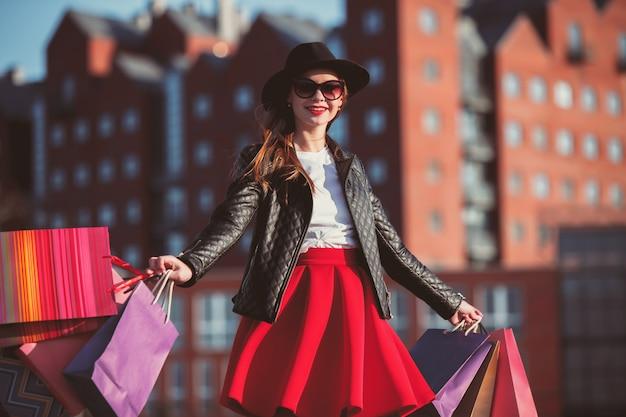 Het meisje dat met het winkelen zakken op stadsstraten bij zonnige dag loopt